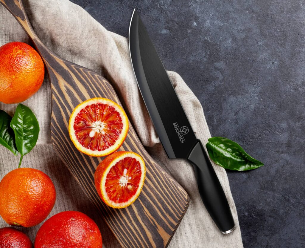 Benchusch Ceramic Knife 7 inch with cutting red orange and the chopping board on the dark background