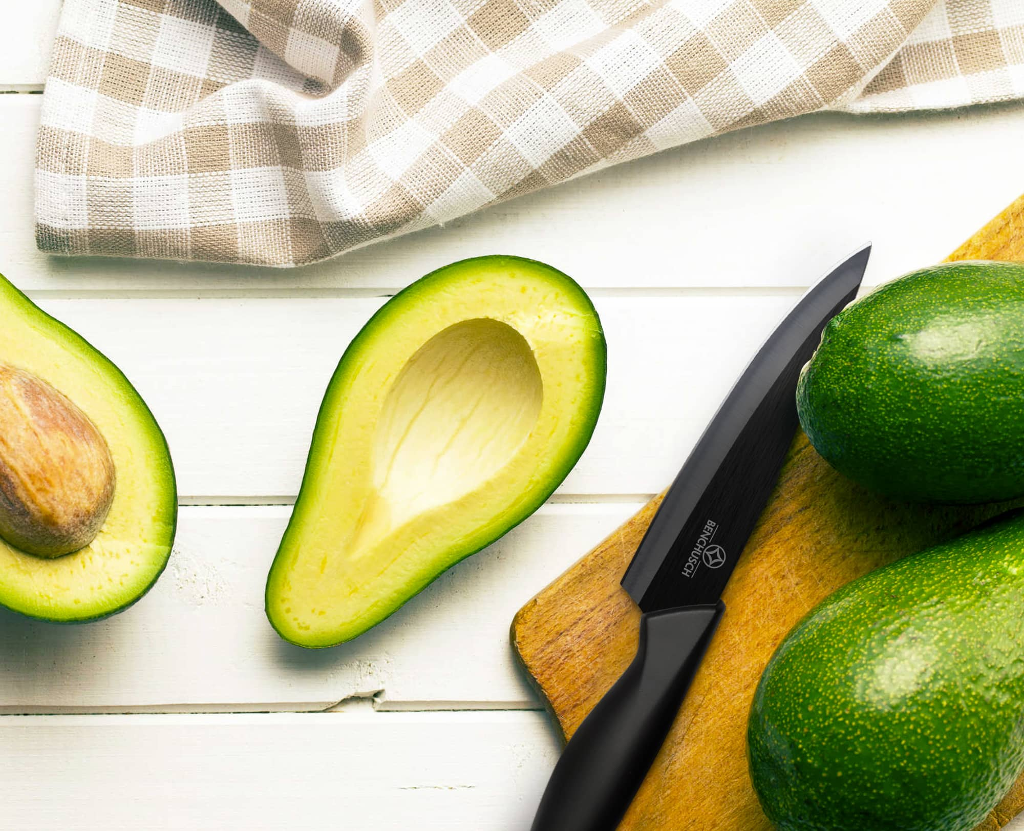Benchusch Ceramic Knife 7 inch with cutting avocados and the chopping board on the bright wood background
