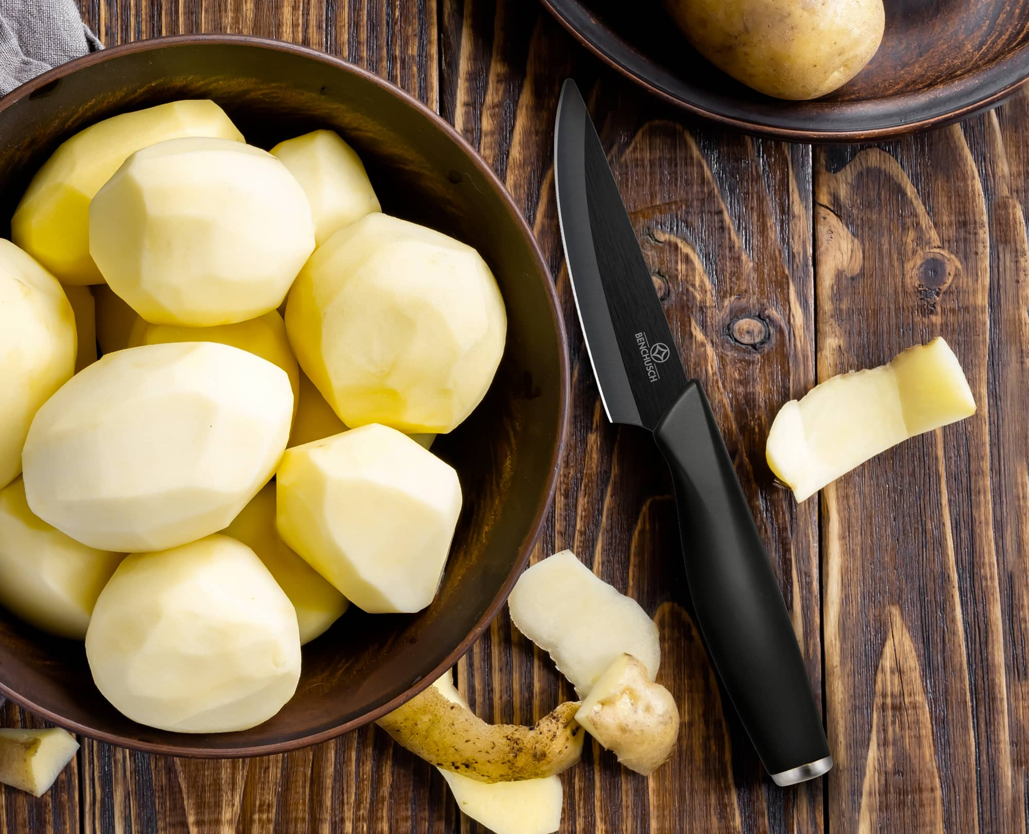 Peeling potatoes with Benchusch Zirconia Series Ceramic Paring Knife on the wooden table