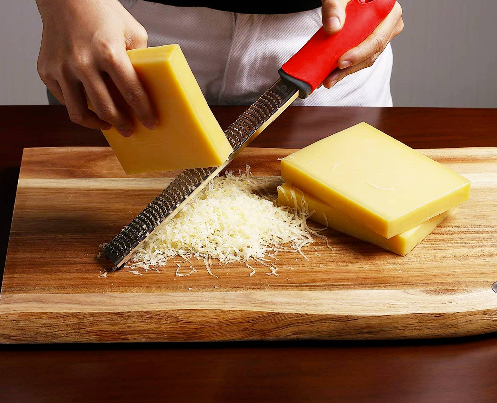 Man is using Benchusch Classic Red Cheese grater to zest the parmesan cheese on the wood chopping board
