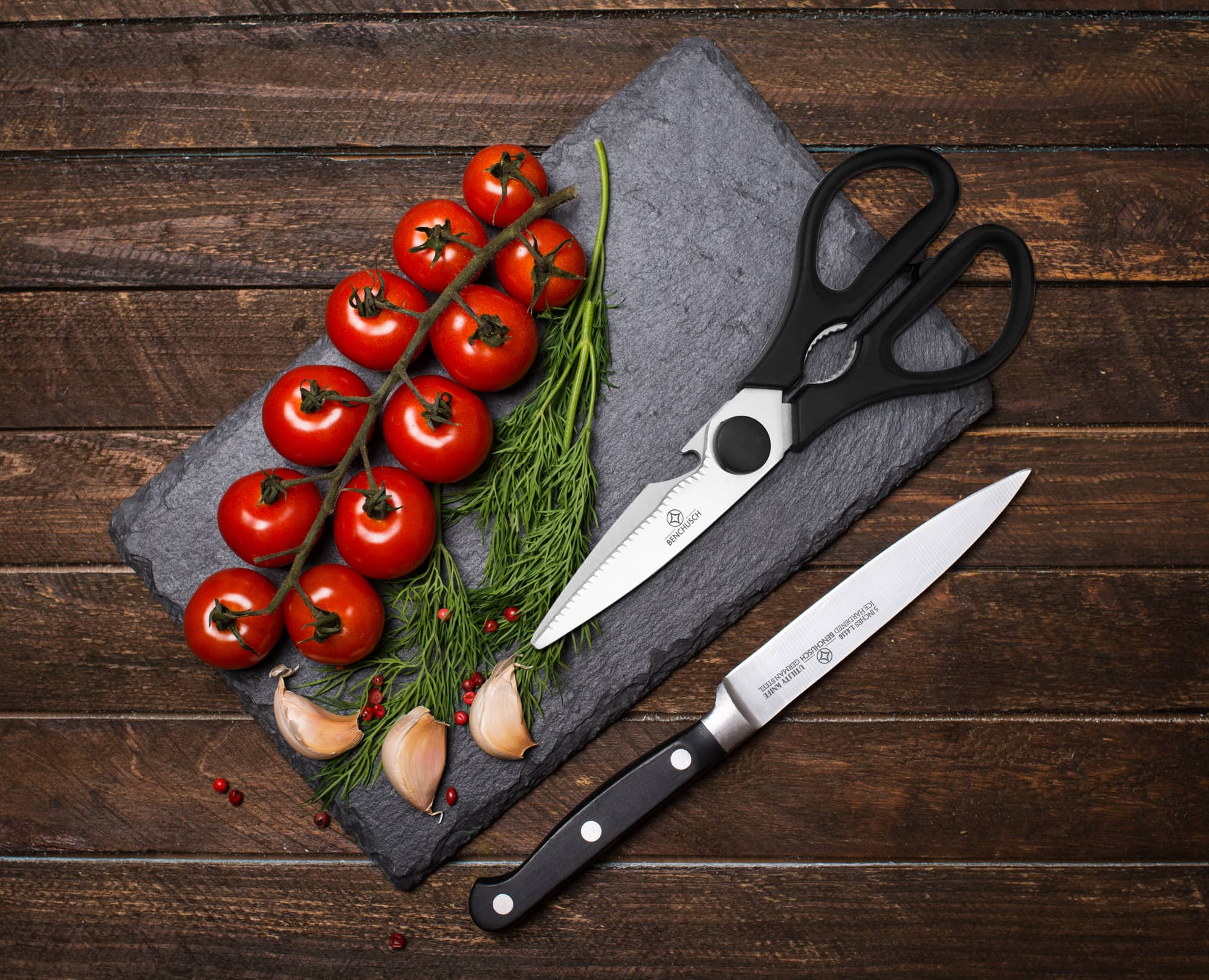 Benchusch Classic 5-inch Utility Knife and 8-Inch Scissors with tomatoes, dills, garlics on the black stone board in the wood background