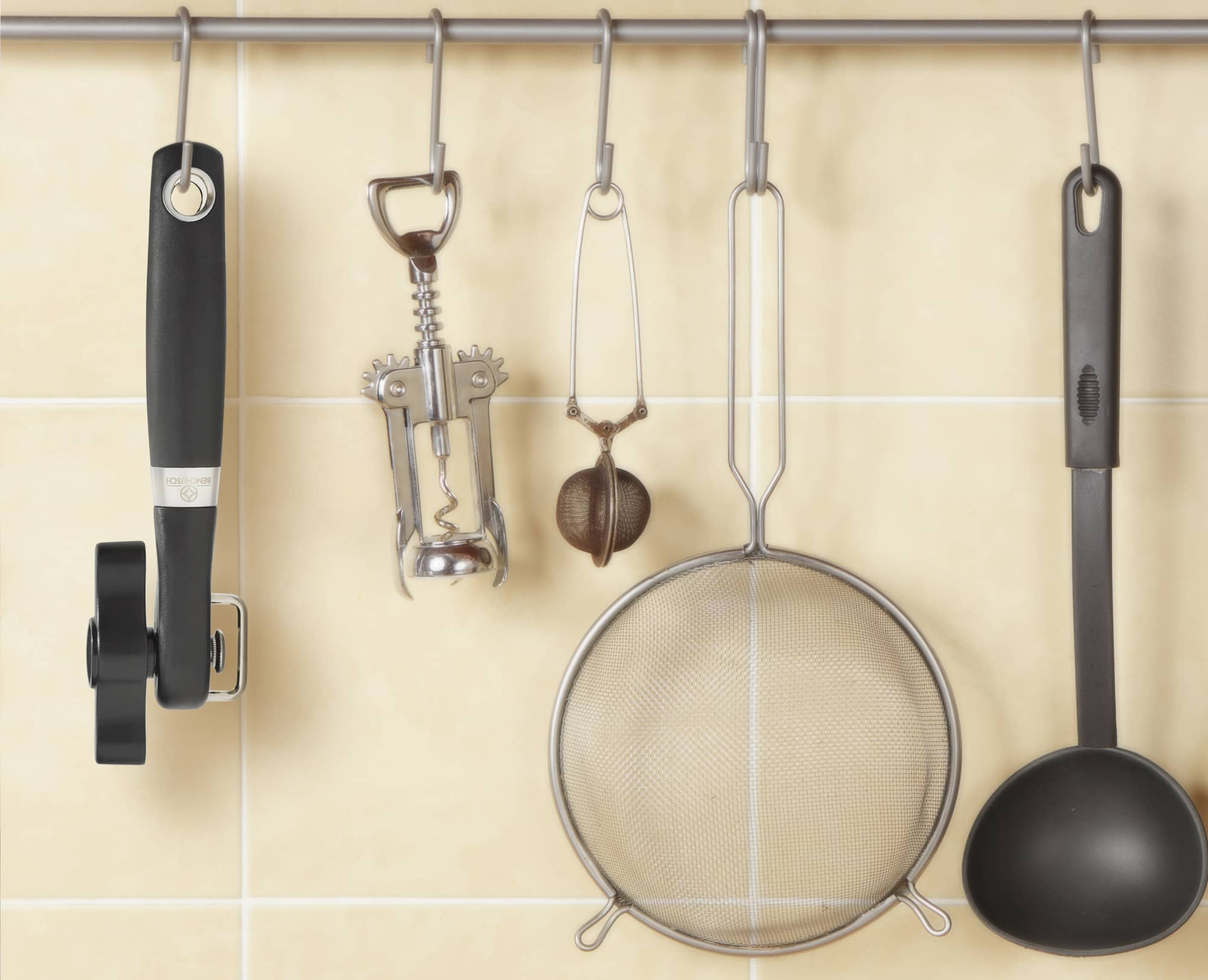 Benchusch Covera Smooth Edge Can Opener is hung on the kitchen with other utensils