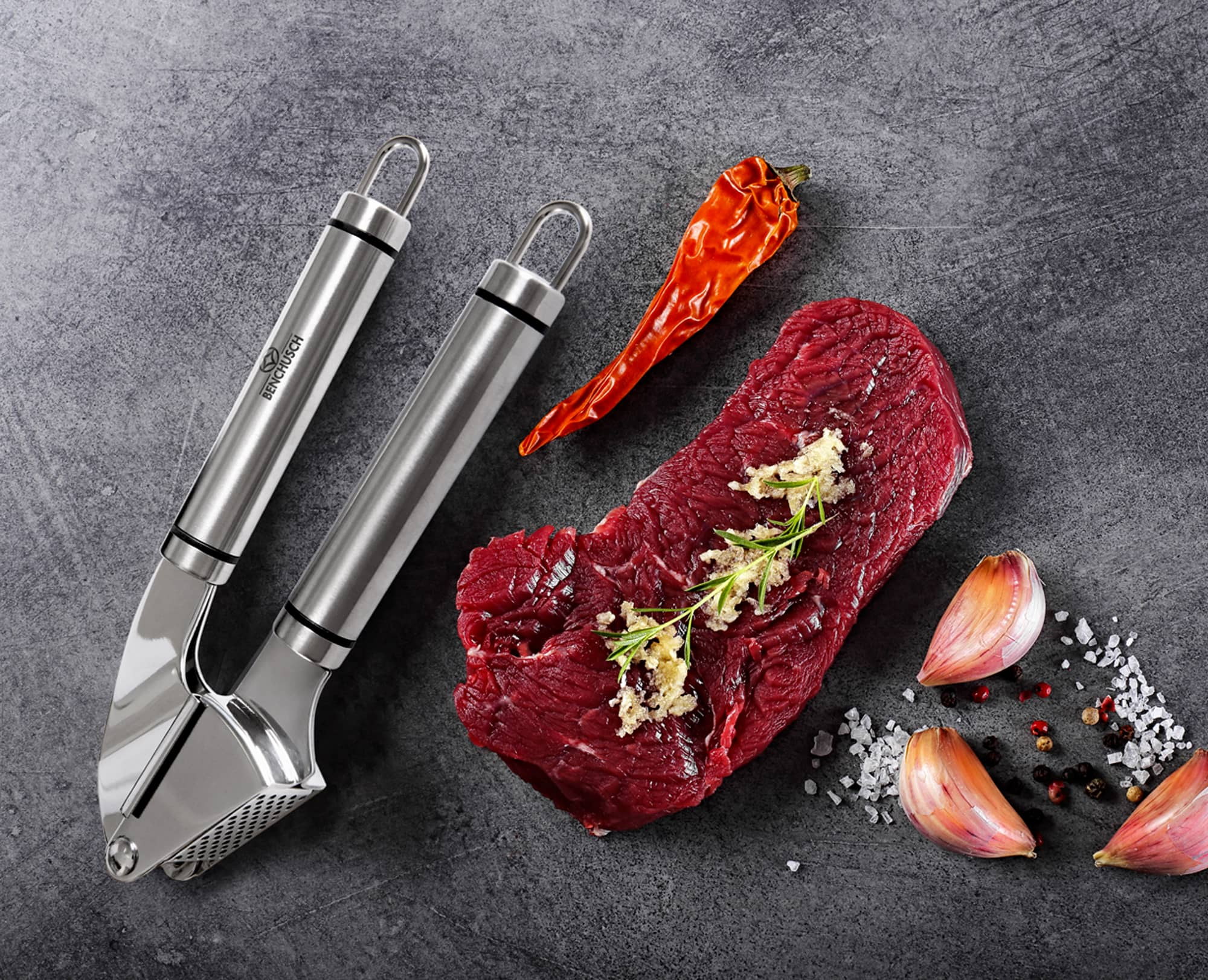 Benchusch garlic press with Beef meat, pepper and minced garlic on the dark background