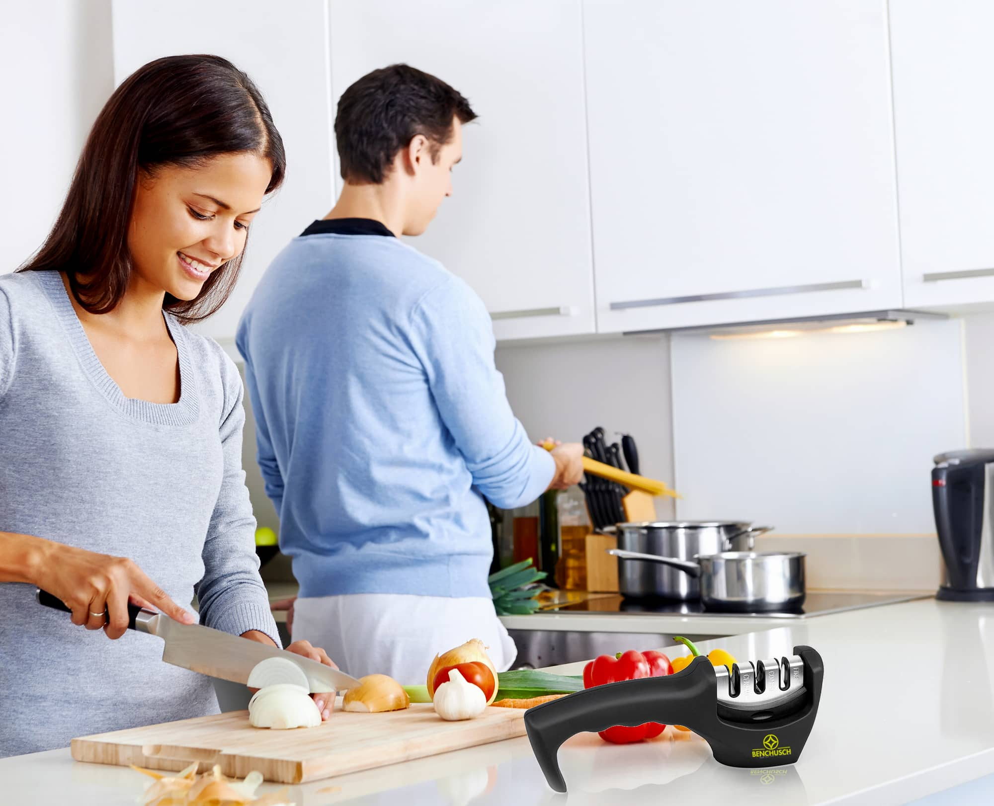 Benchusch Three-Stage Knife Sharpener on table with happy couples are cooking in the kitchen background